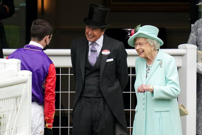 Queen Elizabeth II glundert wanneer ze samen met racing manager John Warren naar de paarden kijkt.