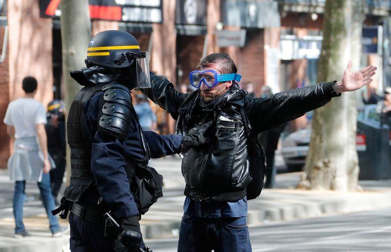 Een demonstrant wordt staande gehouden door politie in Toulouse, Frankrijk, vorige week. Beeld EPA