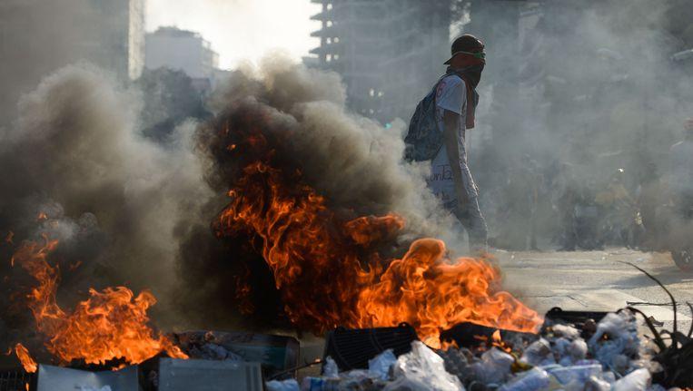 Een demonstrant achter in brand gestoken straatafval in Caracas, Venezuela. Beeld AFP