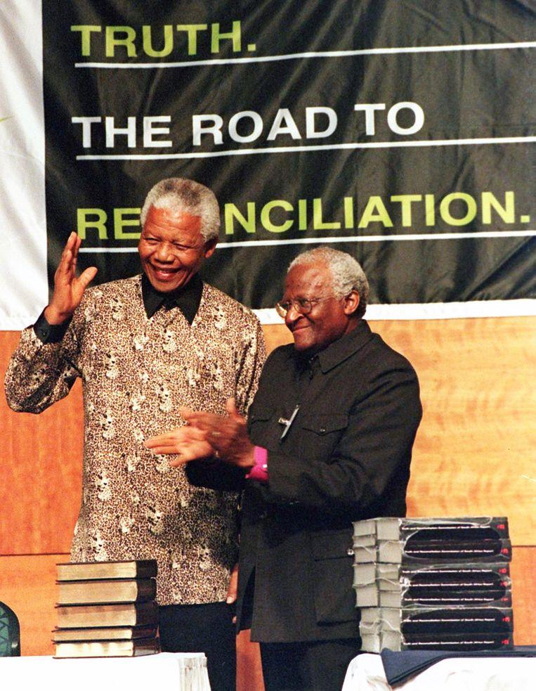 Nelson Mandela ontvangt in 1998 het eerste rapport van de Waarheidscommissie uit handen van voorzitter Desmond Tutu. 'Mandela hield van ubuntu, maar dat wil niet zeggen  dat hij ook altijd handelde in de geest ervan.'  Beeld AFP
