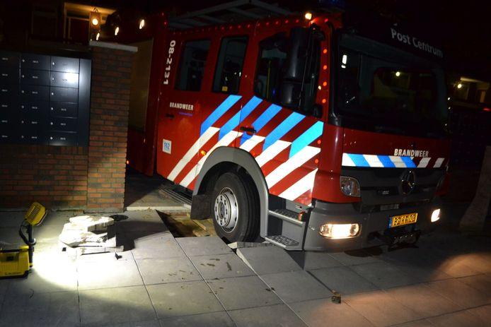 De brandweerwagen op de oprit van het appartementencomplex.