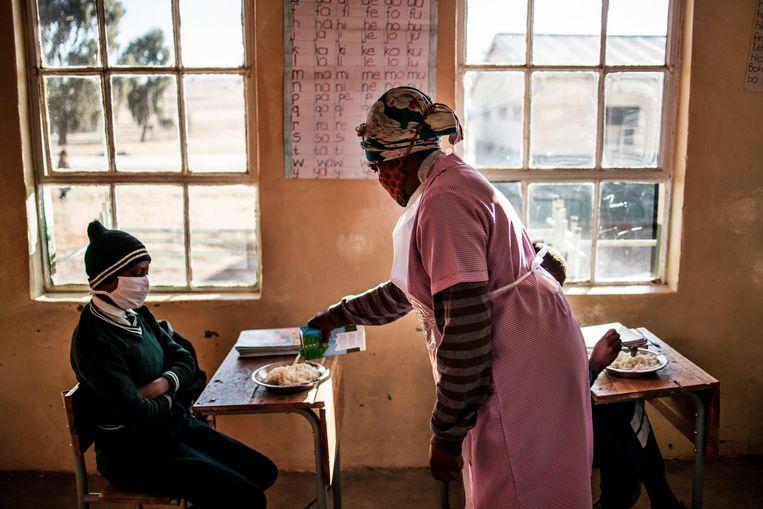Studenten in het Zuid-Afrikaanse Sterkspruit krijgen een bord maïspap te eten. Beeld AFP
