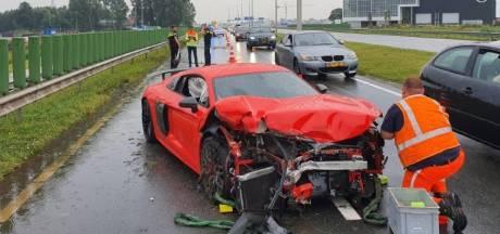 Peperdure Audi R8 knalt tegen vangrail, brokstukken vliegen over de weg
