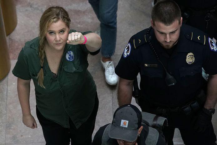 Amy Schumer wordt na haar arrestatie weggeleid.
