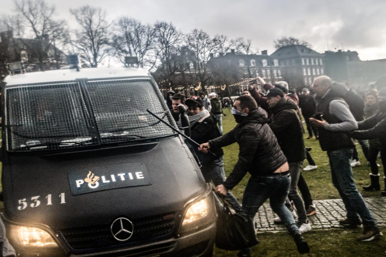 Een politiebusje wordt belaagd tijdens de rellen op het Museumplein in Amsterdam. Beeld ANP