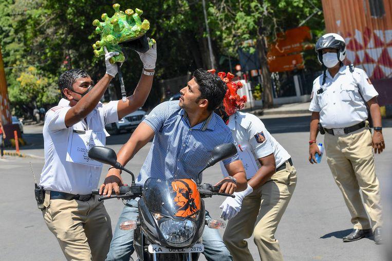 Verkeerspolitie in India dragen een helm in de vorm van het coronavirus bij een verkeerscampagne tijdens de lockdown.  Beeld AFP
