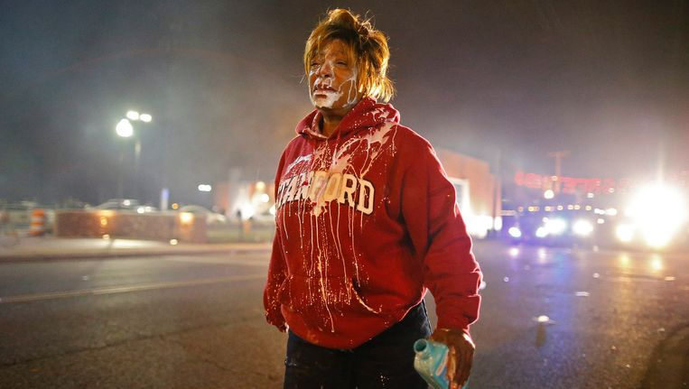Een demonstrant in Ferguson heeft melk over haar gezicht gegoten nadat ze traangas in haar ogen had gekregen. Na het besluit van een jury om een blanke agent niet te vervolgen wegens het neerschieten van de zwarte tiener Michael Brown, afgelopen augustus, braken rellen uit. Er zijn gisteren honderden extra militairen van de Nationale Garde naar Ferguson gestuurd om escalatie te voorkomen. Beeld EPA