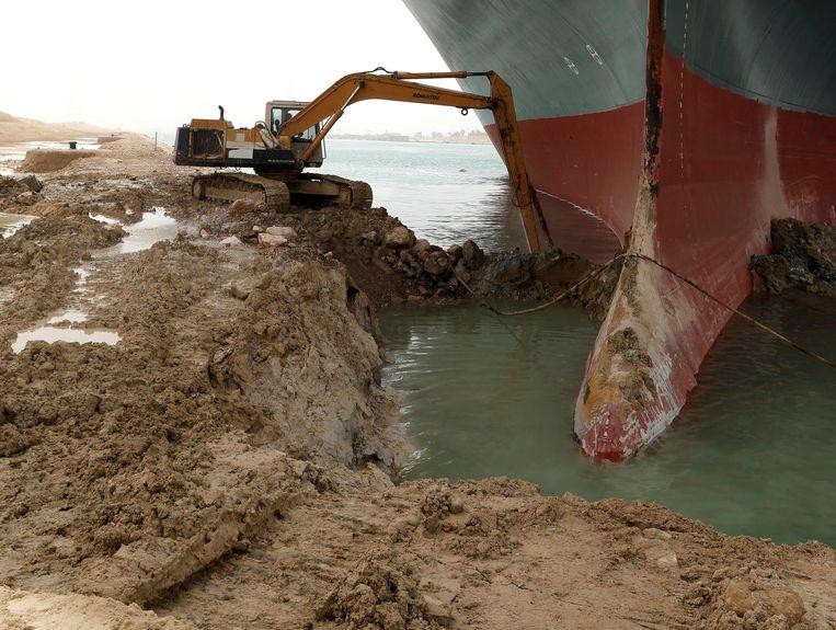 Aan de oever wordt geprobeerd de neus van het schip vrij te maken.  Beeld EPA