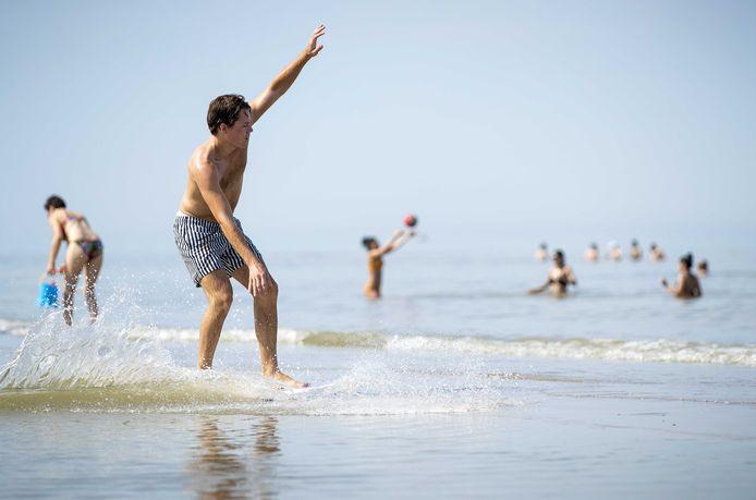 Een man vermaakt zich op het strand. Nu er een periode met zonnig en heet zomerweer is aangebroken, zijn mensen op zoek naar verkoeling.