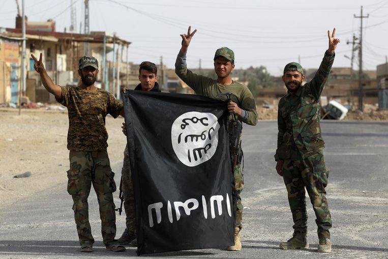 Triomferende Iraakse soldaten houden de vlag van IS ondersteboven in Al Qaim. Beeld AFP
