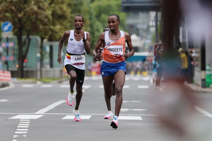 Abdi Nageeye (r) helpt Bashir Abdi (l) in de laatste meters van de olympische marathon.