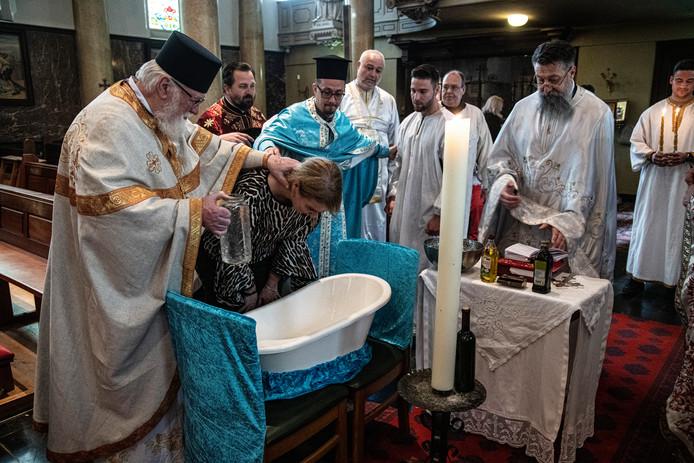 Een vrouw wordt gedoopt tijdens de Servisch-orthodoxe dienst in de Beekse Sint-Bartholomaeuskerk.