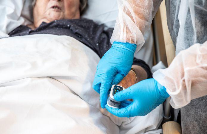 Een verpleegster van een verpleeghuis  verzorgt een coronapatiënt.