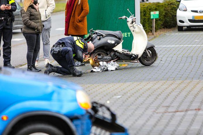 Twee jonge mannen zijn gewond geraakt bij een botsing tussen een auto en een scooter.