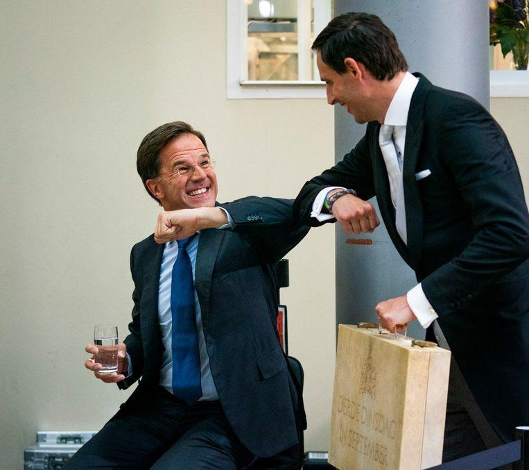 Minister Hoekstra van Financiën en premier Rutte geven elkaar een elleboog na de uitzending van de NOS. Beeld Freek van den Bergh / de Volkskrant