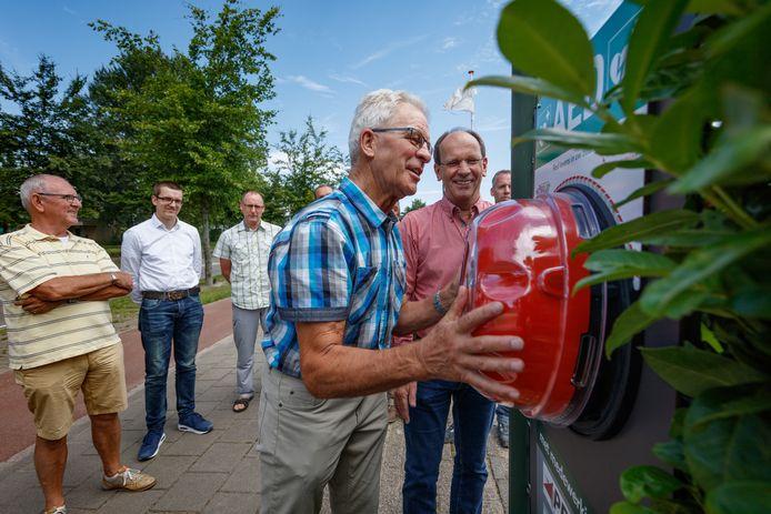 Wim van Ruyven (blauwe blouse) en Eric Tak hangen in 2017 een AED op bij tennisclub Vijfhuizen in Etten-Leur.
