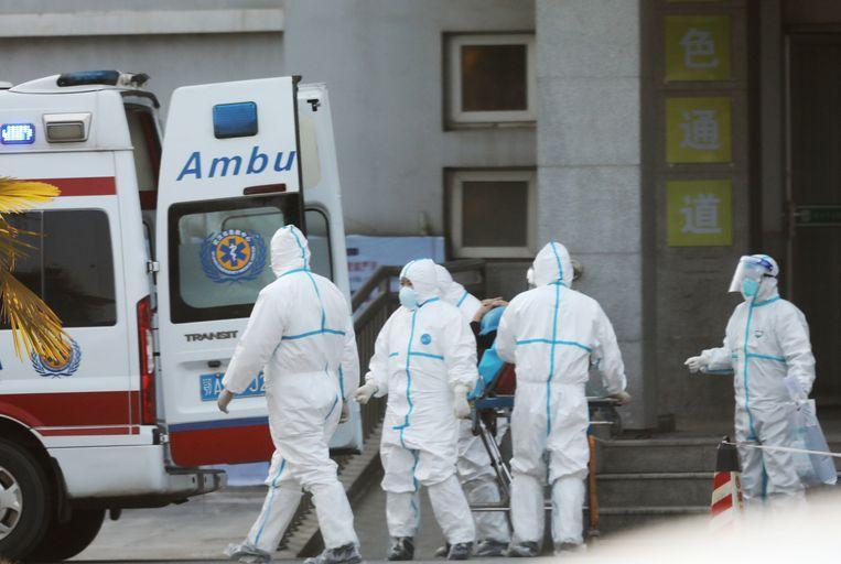 Medisch personeel in Wuhan waar besmette patiënten in het ziekenshuis behandeld worden. Beeld EPA