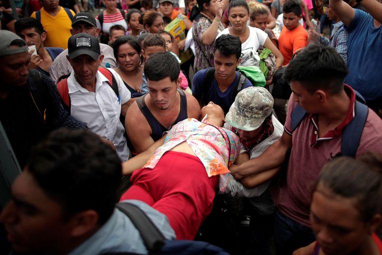 Een vrouw is flauwgevallen in Ciudad Hidalgo, waar ze in de rij stond om asiel aan te vragen in Mexico.  Beeld REUTERS