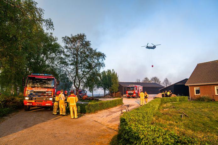 Brandweer probeert vuur bij woningen tegen te houden.