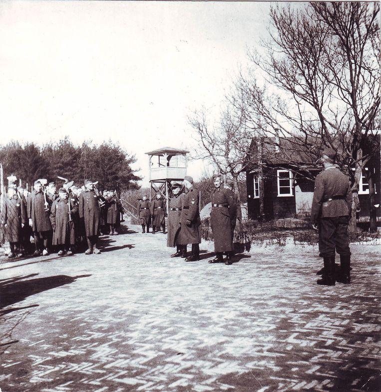 Appèlplaats met gevangenen en wachttoren in Kamp Amersfoort. Beeld