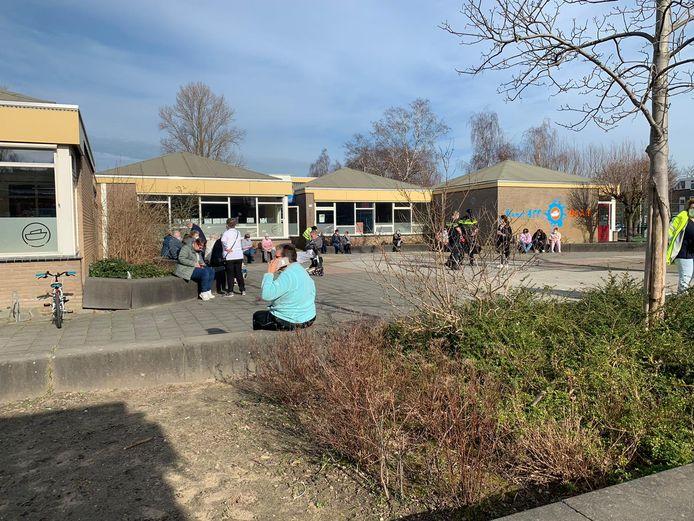 De opgevangen bewoners wachten bij de basisschool.