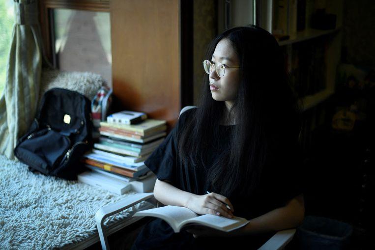Student Lin Xiaobin studeert in haar slaapkamer in de Chinese hoofdstad Beijing. Door een verbod van voormalig president Trump kan ze niet in de VS studeren.  Beeld Hollandse Hoogte / AFP