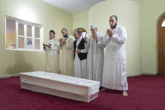 Youssef Bouchikhi (2e links), de broer van Mohammed, bidt met geestelijk leiders en een vriend van Mohammed (rechts), bij de kist in een moskee in Berkane.