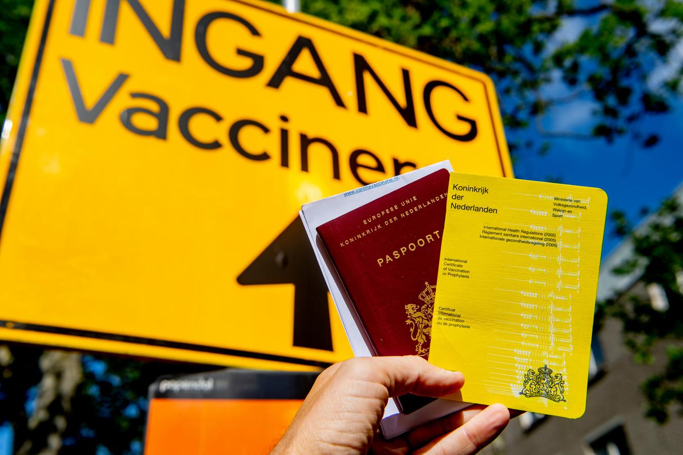 Gele boekje en een paspoort bij een coronavaccinatie lokatie. Hiermee mag men weer reizen in de zomer.