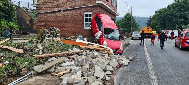 Een auto is door het stromende water tegen de gevel van een gebouw aangegooid in de omgeving van het Belgische Luik. Beeld Walter Weg