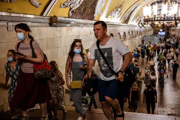 Forensen lopen door de gangen van de Moskouse metro. Sinds kort moeten veel inwoners verplicht een mondkapje dragen.  Beeld Dimitar Dilkoff / AFP