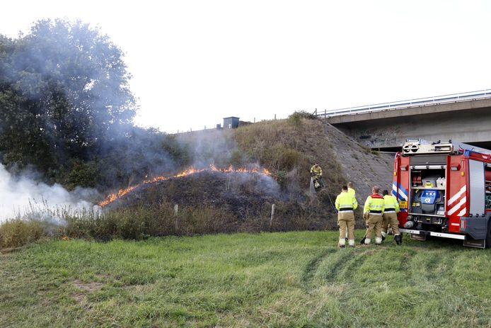 De brandweer aan het werk onder het viaduct van de A77 bij Boxmeer.