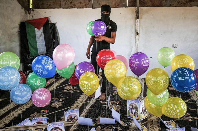 Een gemaskerde Palestijn bereidt brandbalonnen voor die worden opgelaten bij de grens tussen de Gazastrook en Israël in de buurt van de stad Rafah.