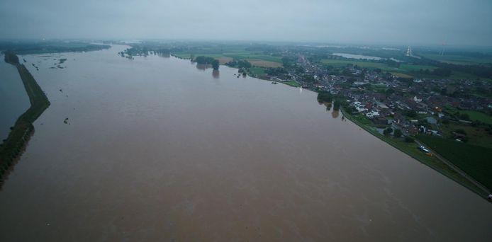 Inwoners van het Maasdorp Kotem, hier rechts in beeld, worden verplicht geëvacueerd. De Maas op de foto is drie keer breder dan normaal.