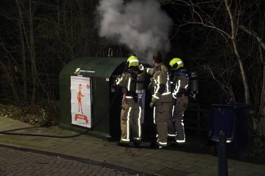 Brandweermannen blussen de container van het Leger des Heils