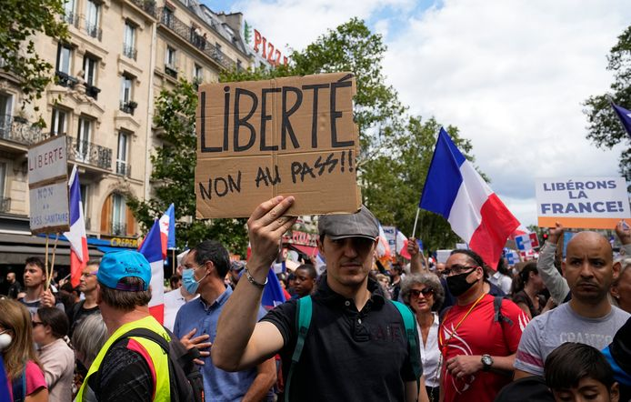 A protestor holds a sign which reads 'freedom, no to the pass' during a demonstration in Paris, France, Saturday, July 31, 2021. Demonstrators gathered in several cities in France on Saturday to protest against the COVID-19 pass, which grants vaccinated individuals greater ease of access to venues. (AP Photo/Michel Euler)
