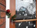 Roos bij de vernielde voordeur. Buurtbewoners leven mee met de slager.