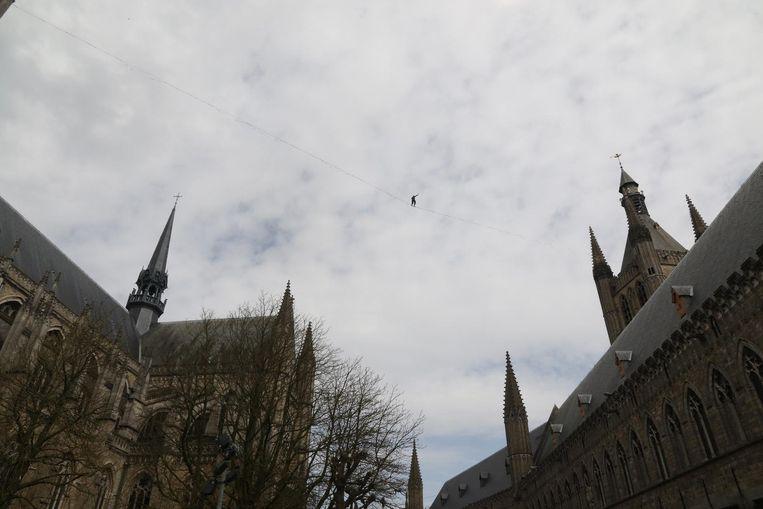 Het stipje in de lucht is wel degelijk een koorddanser die behoedzaam tussen kathedraal en belfort stapt.