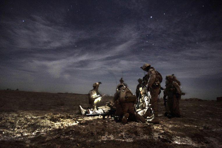 Een groep Amerikaanse militairen wacht in Afghanistan op een medische helikopter, een van hen is gewond geraakt door een explosief verstopt in de grond.  Beeld AFP