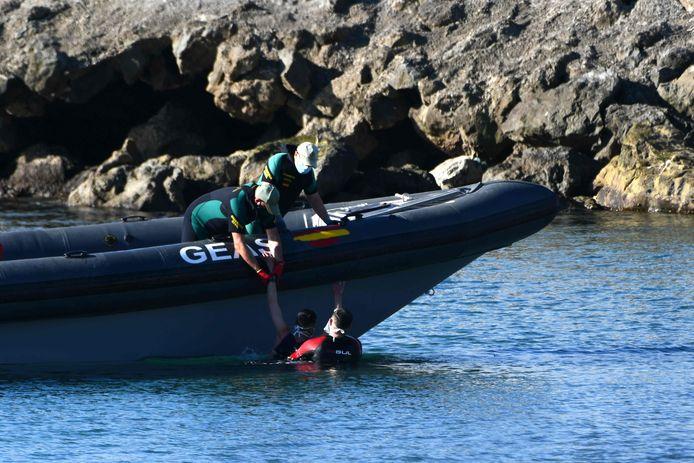 Leden van de Spaanse Guardia Civil halen twee migranten uit de zee.