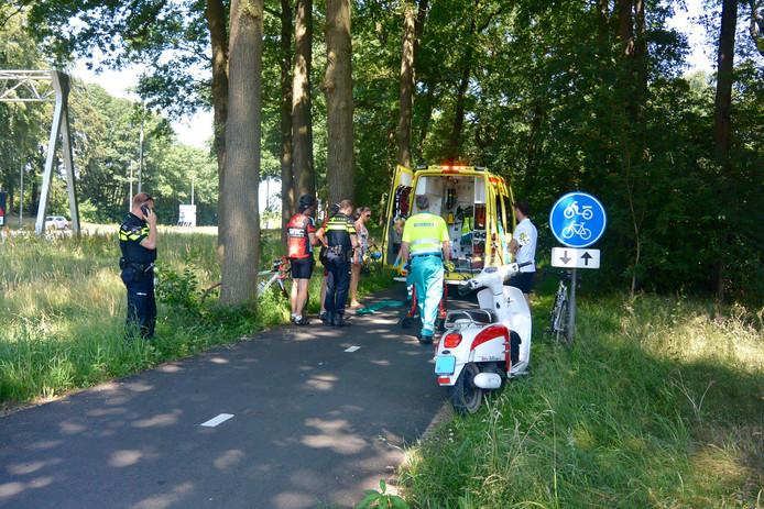 Ambulance- en politiemedewerkers verlenen hulp aan de wielrenners.