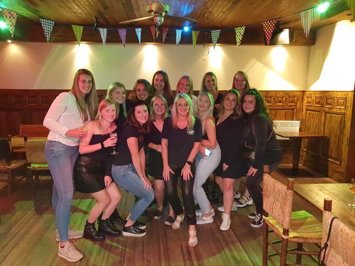Groepsfoto Jong Dames 1 van MHC Rapide bij café Lazarus in Sint Jansteen. In het midden Lazarus-eigenaresse Daniella, sponsor van het team.