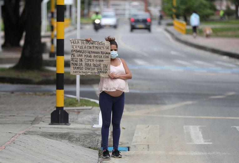 Bogota, Colombia. De Venezolaanse Veronica Hernandez, 20 jaar oud en acht maanden zwanger, houdt een bord omhoog waarop ze vraagt om voedsel of geld. Beeld AP