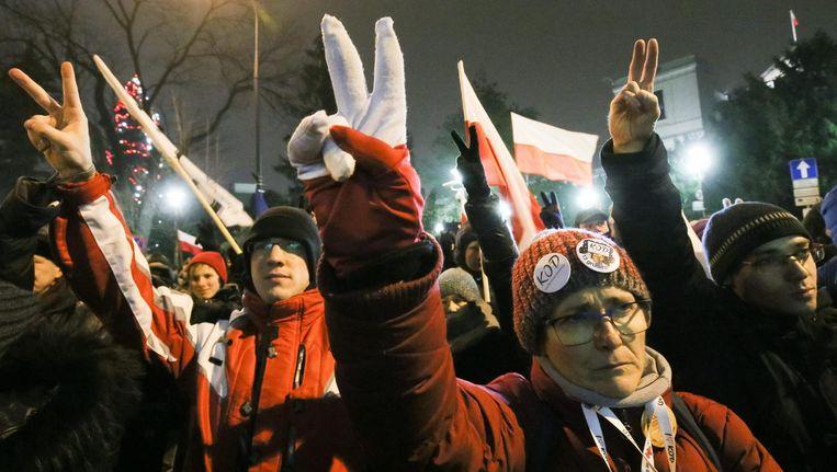 Polen demonstreren vanwege de beperking van persvrijheid voor het Sejm in Warschau. Beeld EPA