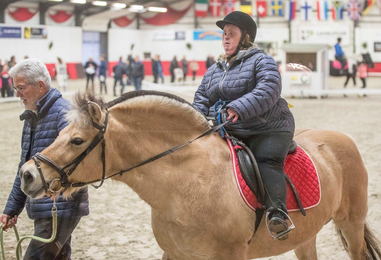 Jolande Oosterling uit West-Souburg doet haar best tijdens de proef met paard Ymea en vrijwilliger Jan. Het levert Jolande een tweede plaats op tijdens de 25e Promotiedag Paardensport Gehandicapten in Nieuw- en Sint Joosland.