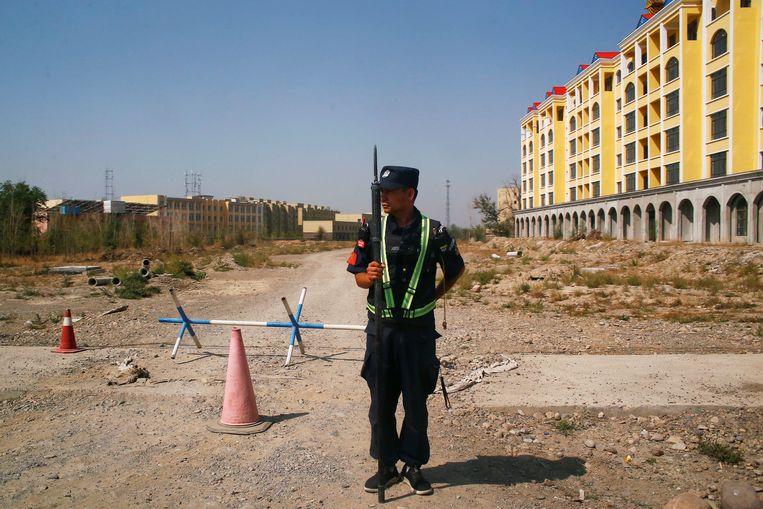 Een Chinese politieman staat op wacht bij wat officieel een 'beroepsopleidingscentrum' is in Yining, in de grensprovincie Xinjiang. Beeld REUTERS