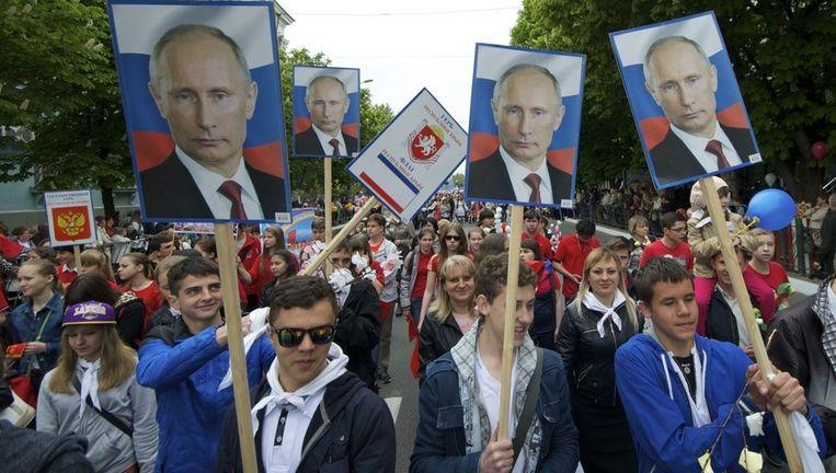 Demonstranten lopen met foto's van de Russische president Vladimir Poetin door Simferopol, de hoofdstad van de Krim. Beeld AP