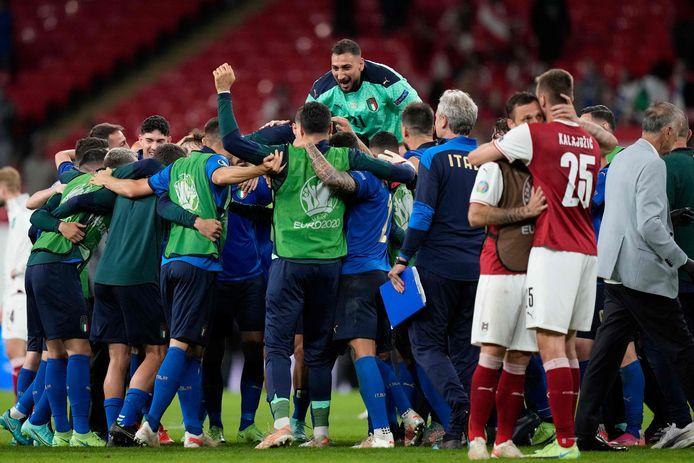Spelers van Italië vieren de overwinning, spelers van Oostenrijk (in het rood) balen.