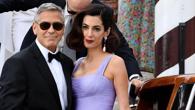 George Clooney en zijn echtgenote Amal verlaten het Cipriani Hotel in Venetië waar Clooney zijn nieuwste film voorstelt. Beeld epa
