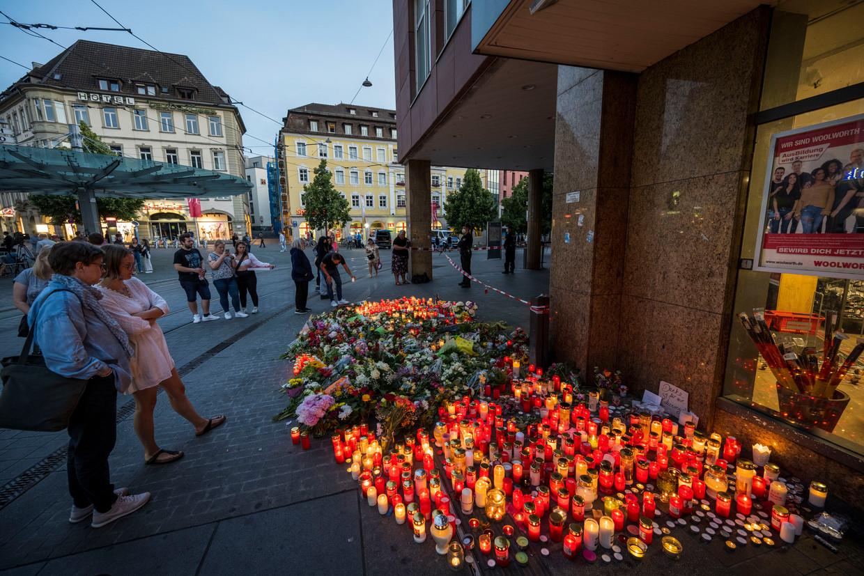 Mensen leggen bloemen en kaarsen neer waar vorige week een Somalische vluchteling drie mensen vermoordde en zeven personen verwondde. Beeld Getty Images