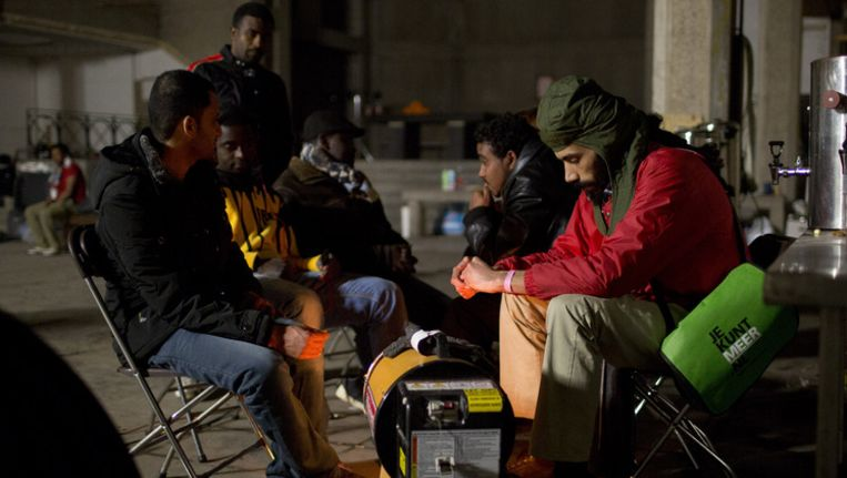 Uitgeprocedeerde asielzoekers zoeken warmte bij een straalkachel in de leegstaande gekraakte St. Josephkerk in Amsterdam. Het pand werd gekraakt en, net als in Den Haag, gebruikt voor opvang. Beeld ANP